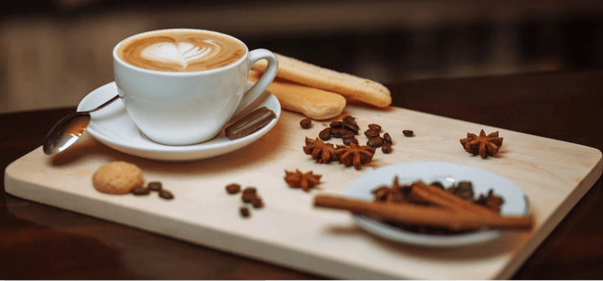 a cup of coffee on a wooden tray