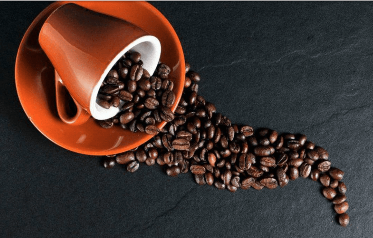 Spilled coffee beans and cup