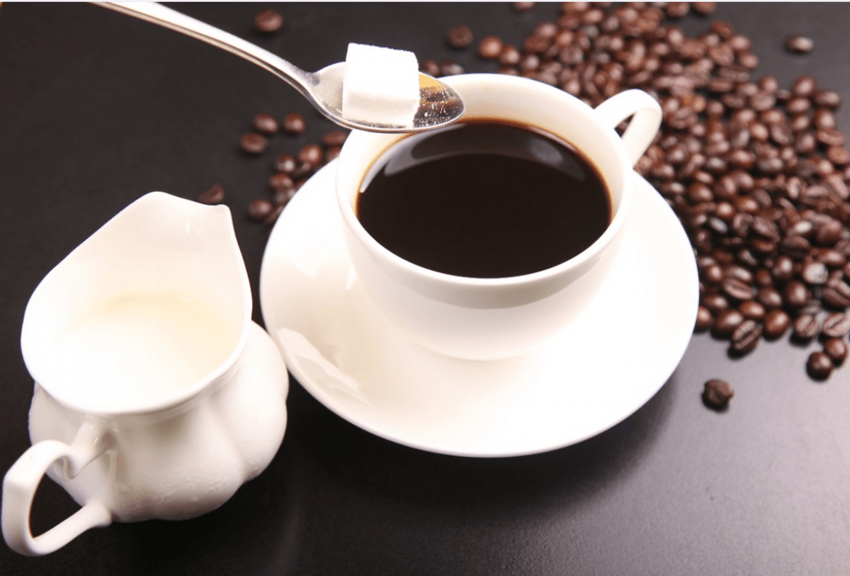 sugar, milk and coffee in a cup
