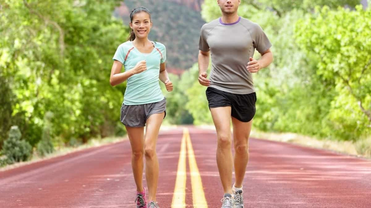 A man and woman jogging on a road with plants on the sides