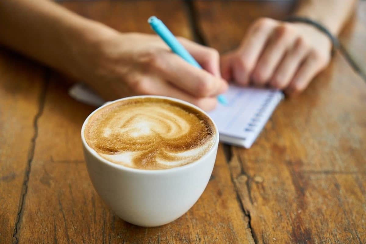 A man writing in a pad and a cup of coffee.