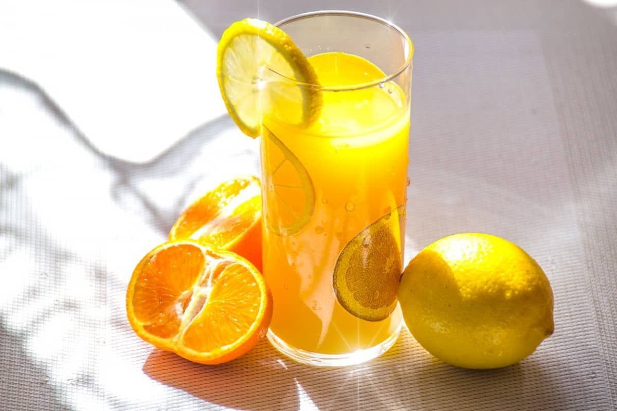 Lemons and oranges with a glass filled with a citrus drink