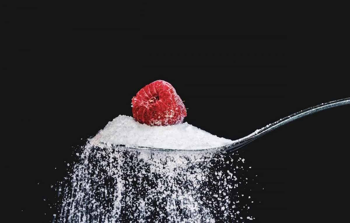 Sugar in a spoon with a raspberry on top.
