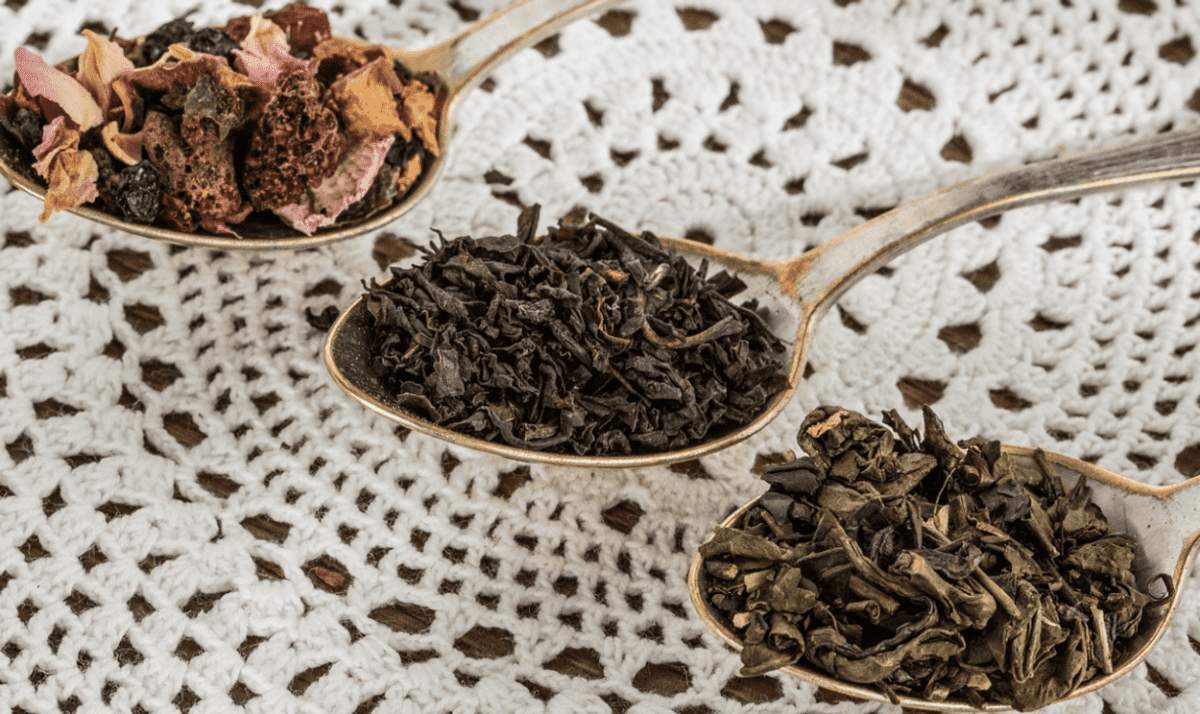 Different types of dried tea leaves are in three different teaspoons.